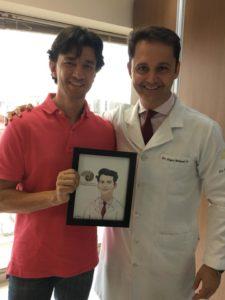 Eduardo, com o médico que fez o implante coclear que lhe permitiu realizar o sonho de ouvir (Foto: Reprodução do Facebook)